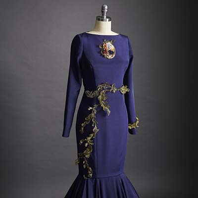 A navy blue crepe de chine dress featuring a sweeping fishtail train. The embroidery, a combination of golden French lace and wire, delicately wraps around the waistline of the dress.