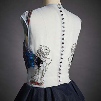 Two hand-embroidered sphinges with multifaceted seed beads appear facing each other on the back of the light blue silk organza bodice that is supported by a navy blue tutu made out of 17 layers of Italian soft tulle. On the front of the dress, a mixture of natural and hand-dyed goose feather create the illusion of a flying eagle.